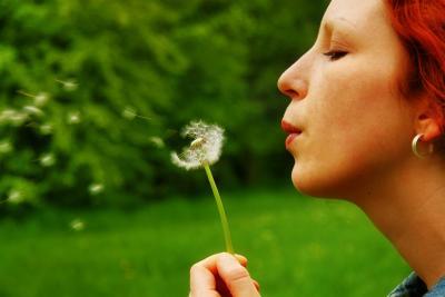 Eine Frau pustet eine Pusteblume