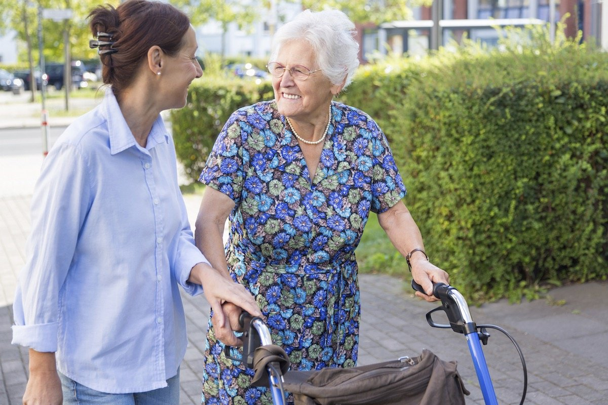 Eine lächelnde Seniorin draußen mit einem Rollator unterhält sich mit einer jüngeren Frau