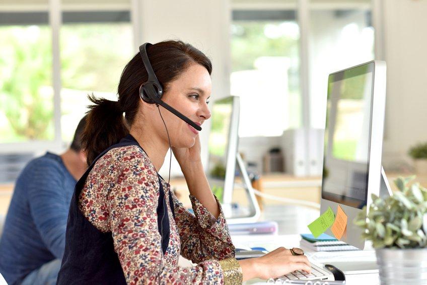 Eine junge Frau mit einem Headset auf vor einem Rechner