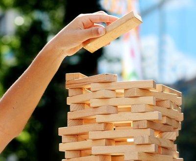 Eine Hand mit einem Jengablock über einem aus Jengablöcken gebauten Turm