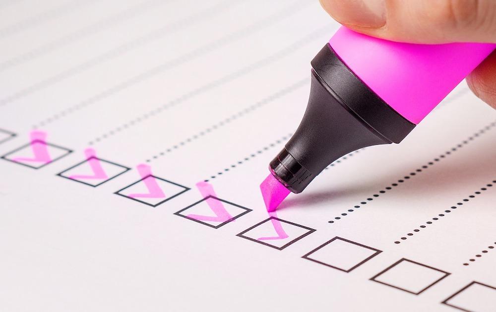 Eine Checkliste mit Kästchen wird mit einem rosa Textmarker abgefertigt