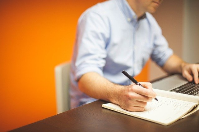 Ein Mann macht Notizen während er etwas auf einem Laptop recherchiert