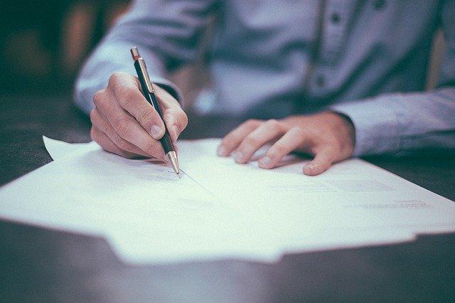 Ein Mann in einem Hemd füllt Dokumente an einem Schreibtisch aus