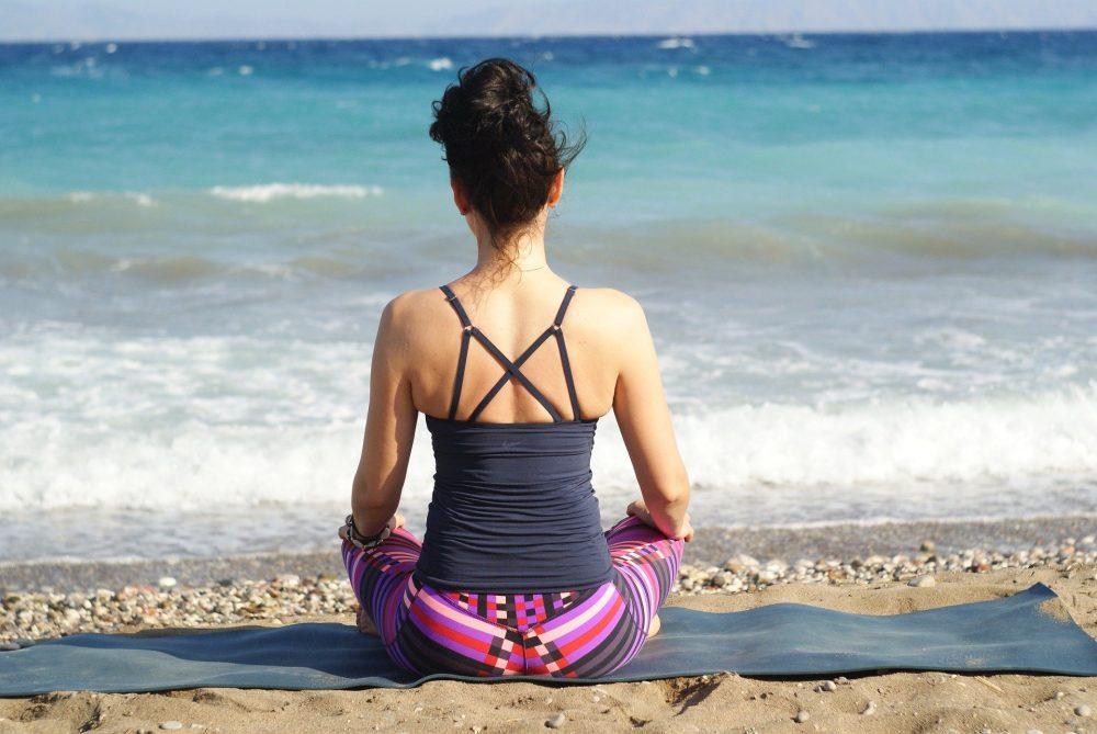 Eine Frau in Sportkleidung sitzt auf dem Strand am Meer im Schneidersitz auf einer Matte