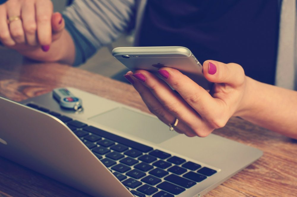Eine Frau mit einem Smartphone in der Hand vor einem Laptop