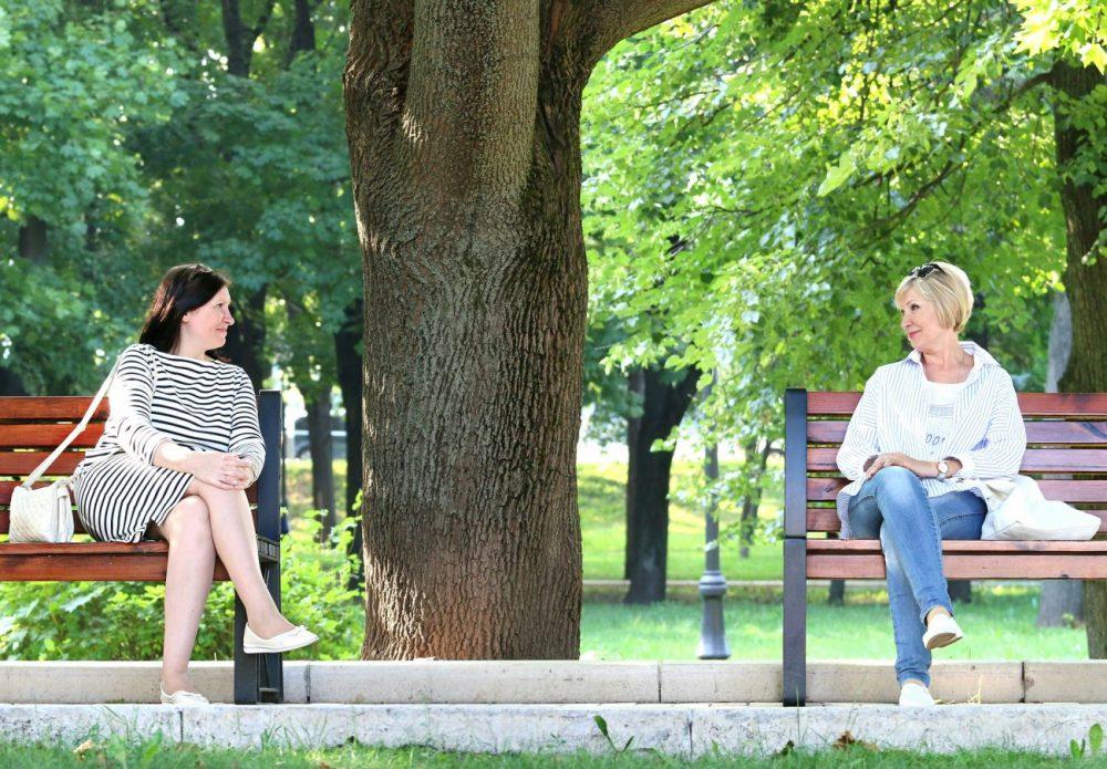 Zwei Frauen sitzen jede alleine auf einem Sitzbank im Park und schauen sich an