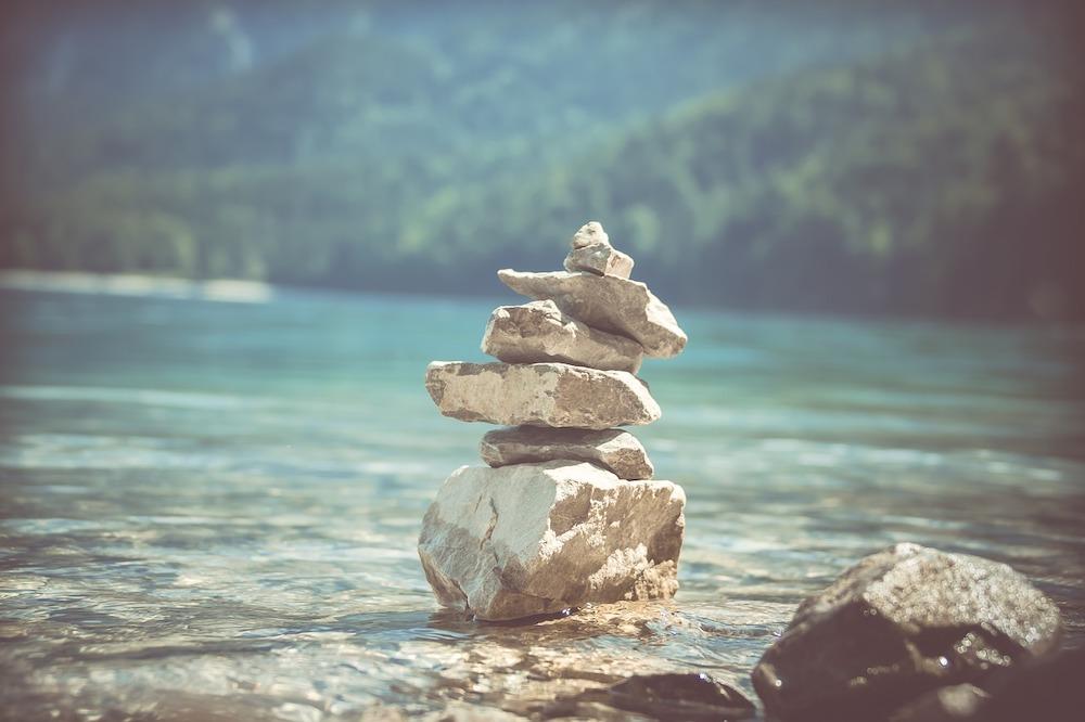 Steine im Gleichgewicht aufeinander gestapelt vor einem Fluss