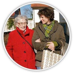 Eine Seniorin geht mit einer jüngeren Frau spazieren