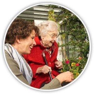 Eine Seniorin mit einer jüngeren Frau schauen sich rote Rosen bei einem Spaziergang an