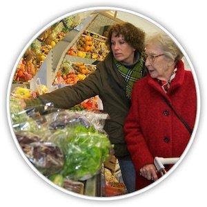 Eine Seniorin wird beim Einkaufen in einem Supermarkt von einer jüngeren Frau betreut