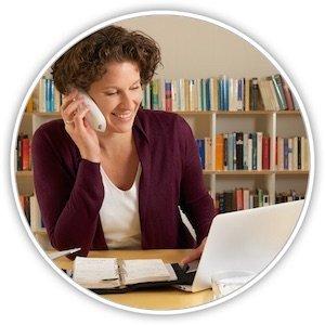 Eine Junge Frau an einem Schreibtisch vor einem Laptop mit einem Telefon am Ohr
