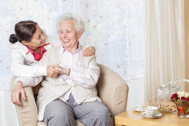 Eine Seniorin im Sessel umarmt von hinten von einer jüngeren Frau umarmt