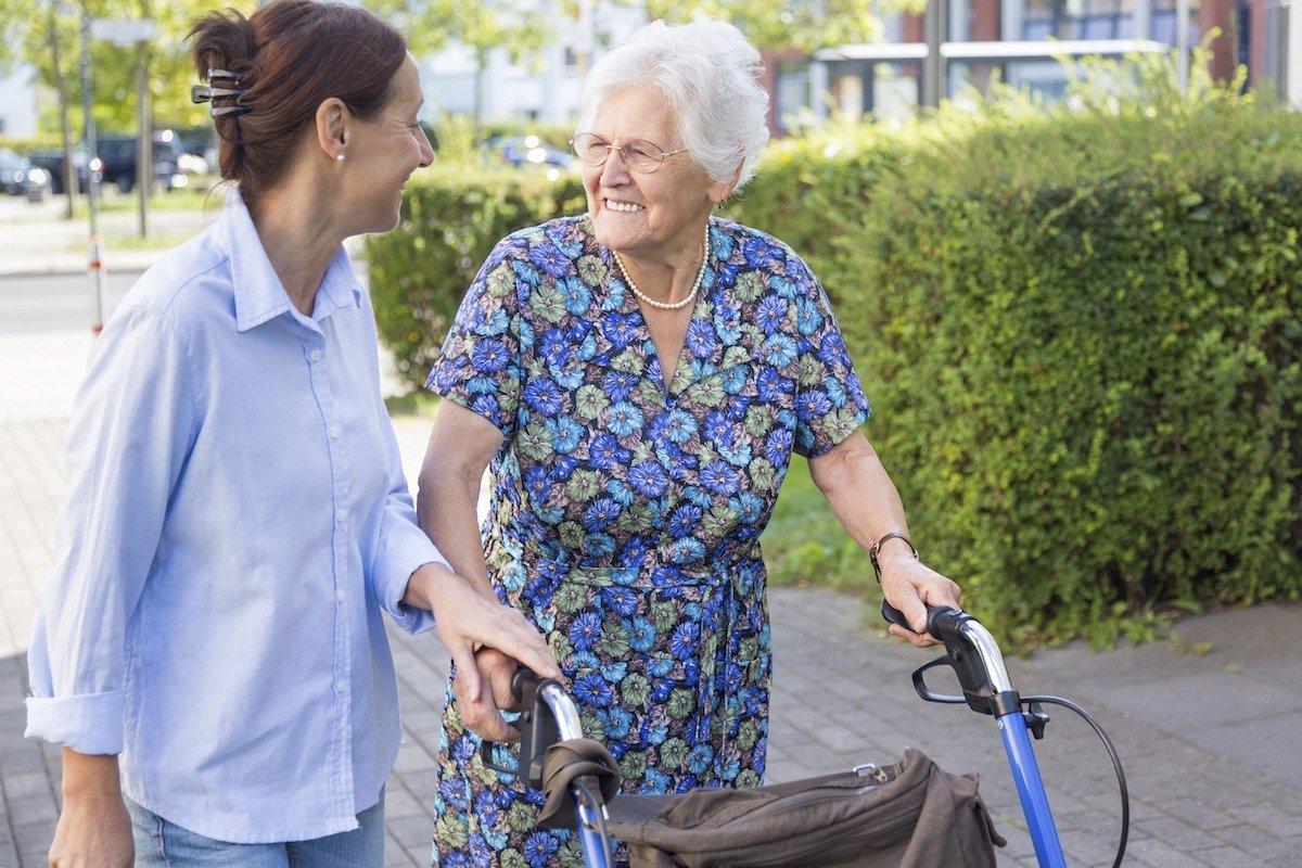 Eine Seniorin mit Rollator begleitet von einer jüngeren Frau