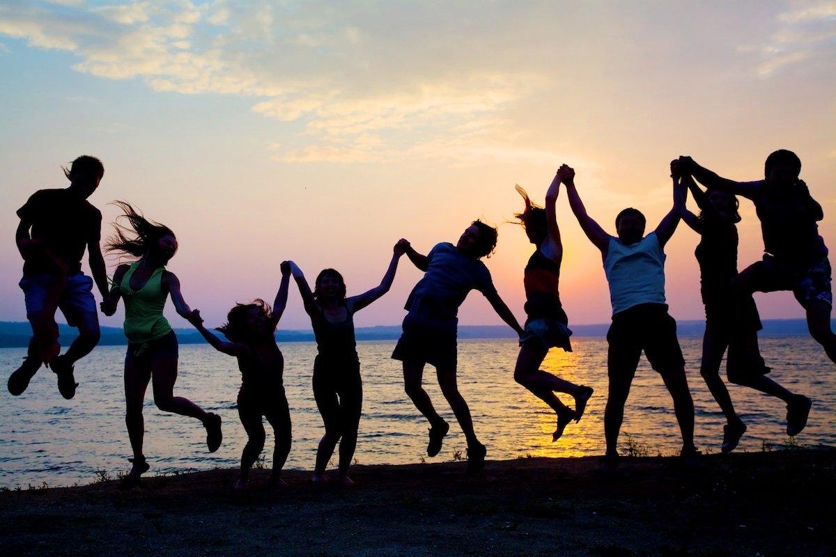 Sihlouetten winer Gruppe von Hände haltenden Menschen die beim Sonnenuntergang hochspringen