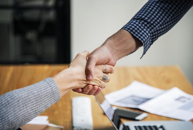 Händedruck zwischen einem Mann und einer Frau über einem Schreibtisch