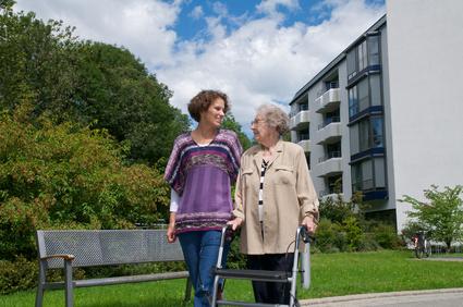 Eine Seniorin mit Rollator wird von einer jüngeren Frau beim Spazieren begleitet
