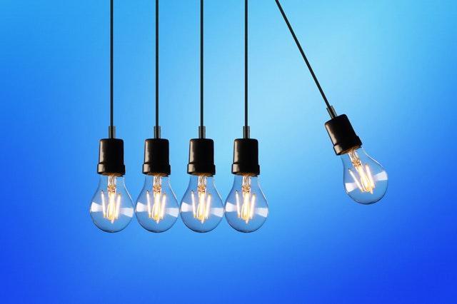 Hängende Glühbirnen die einen Kugelstoßpendel darstellen