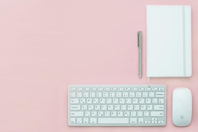 Eine Tastatur, eine Maus, ein Kugelschreiber und ein Heft schön angeordnet auf einem rosa Hintergrund