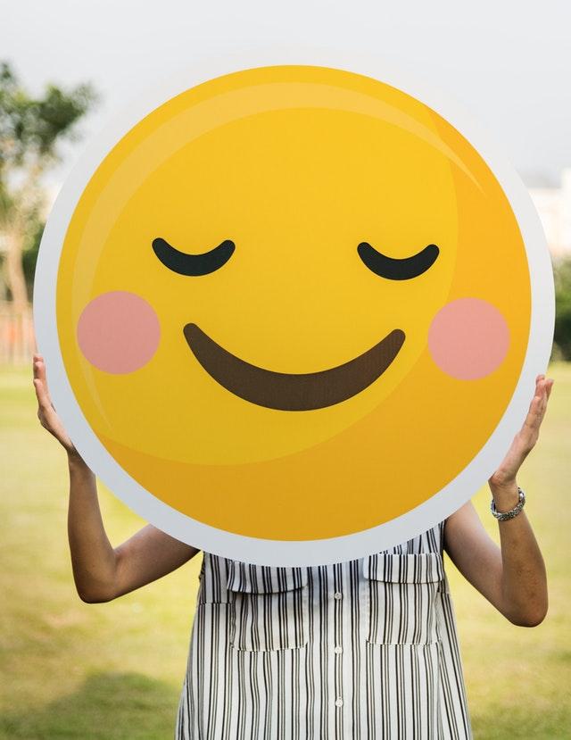 Eine Frau mit einem lächelndem Smiley vor dem Gesicht