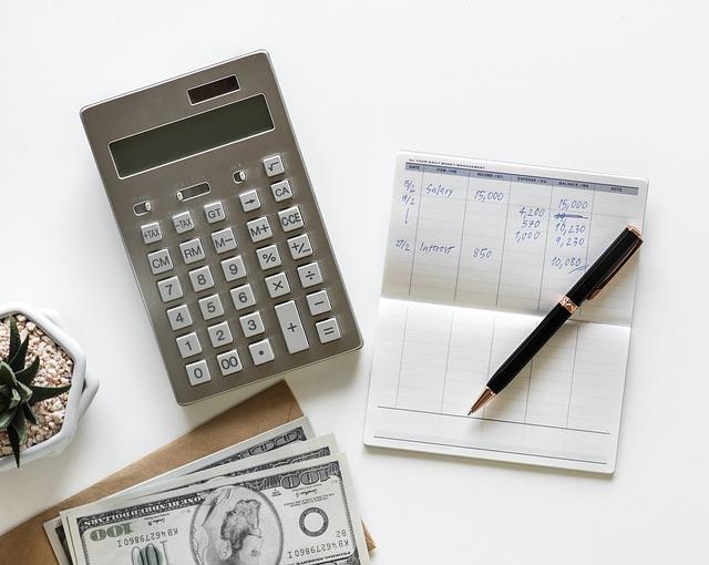 Ein Taschenrechner neben einem Notizblock mit einem Kugelschreiber drauf.