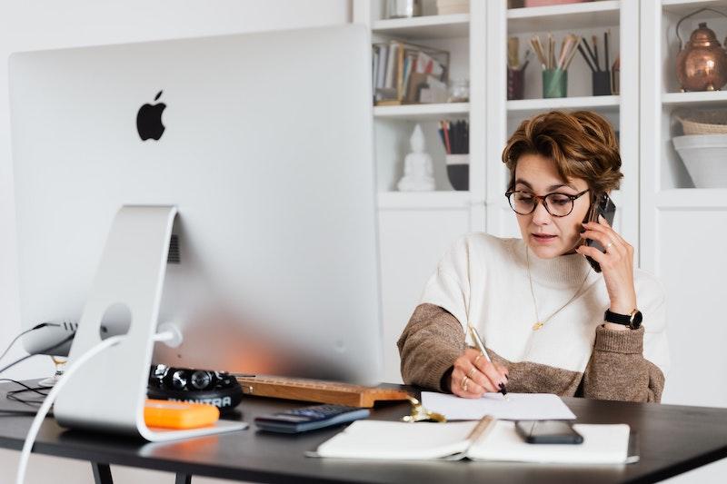 Frau sitzt am Schreibtisch vor dem PC und telefoniert und notiert sich etwas auf dem Notizblock